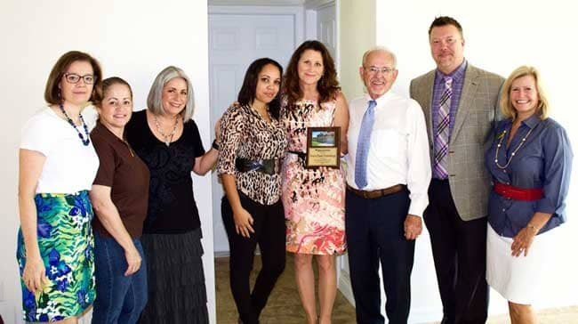 L-R: Norris Furniture & Interiors team Alice Matheson, Tammy Gonzalez, Lorraine Weiss, homeowner Yaseli Torres, Renee and Larry Norris, Doug Ulrich and ...
